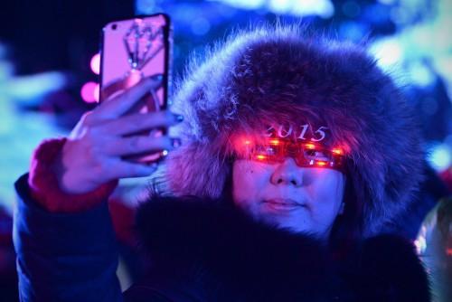 Une chinoise prend un Selfie pendant le compte à rebours du Nouvel An devant le Stade national de Pékin