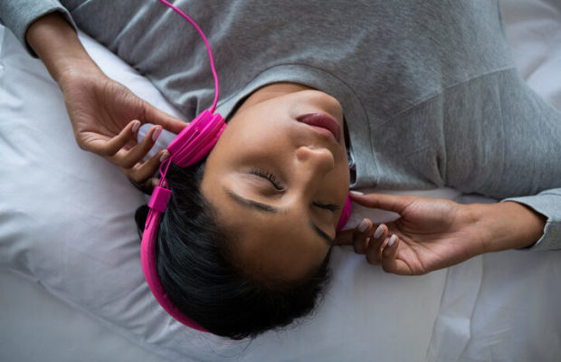 Woman listening to music while sleeping on bed